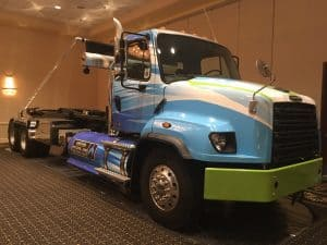 heavy-duty Freightliner CNG trash roll-off hoist truck on display
