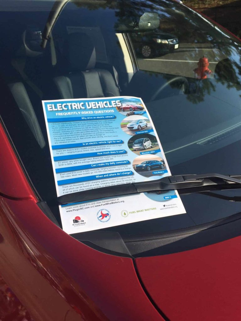 Electric Vehicle frequently asked question pamphlet on a red car